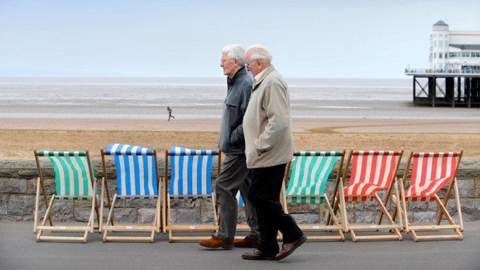 Two older men walk past deckchairs lined up next to a wall by a beach.