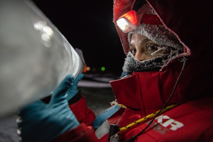Maria Josefa Verdugo in polar outfit holds up an ice core