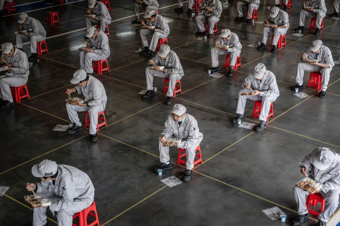 Factory workers in China eat their lunch under social distancing restrictions sitting on spaced out red stools