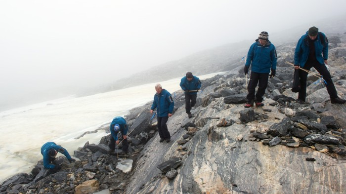 Six people in blue coats use sticks to search for objects among rocks next to an expanse of ice.