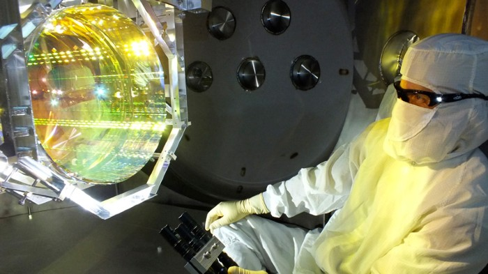 A person in a clean-room suit and goggles looking at an optical device a little bigger than their head.