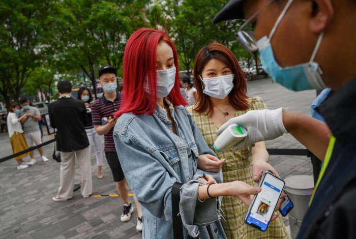 Women in Beijing display a health QR code on their phones as a security guard takes their temperature with a remote sensor