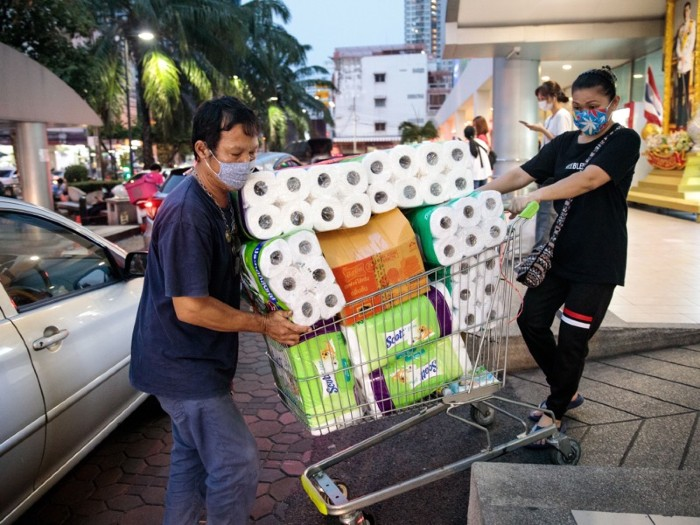 People wearing face masks manoeuvre a shopping trolley piled high with rolls of paper out of a supermarket.