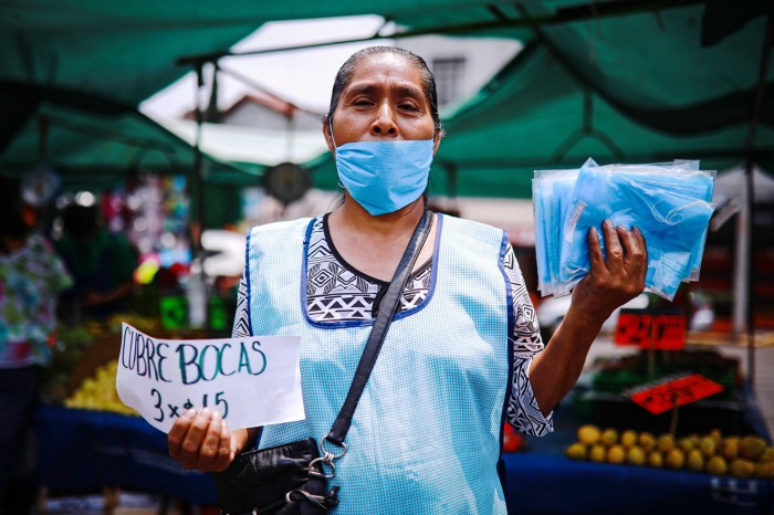 A woman wearing a face mask and apron sells face masks at a market in Mexico city
