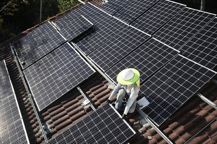 Person in wide-brimmed hat installing solar panels on the roof of a house.