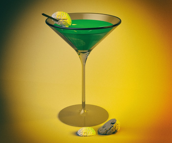 A cocktail glass containing a green liquid, with a small brain on a cocktail stick perched on the rim
