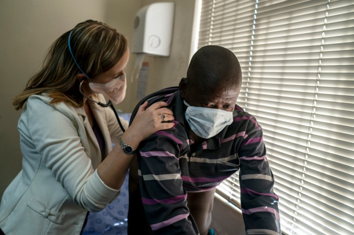 A doctor listens to the lungs of a patient with tuberculosis with a stethoscope