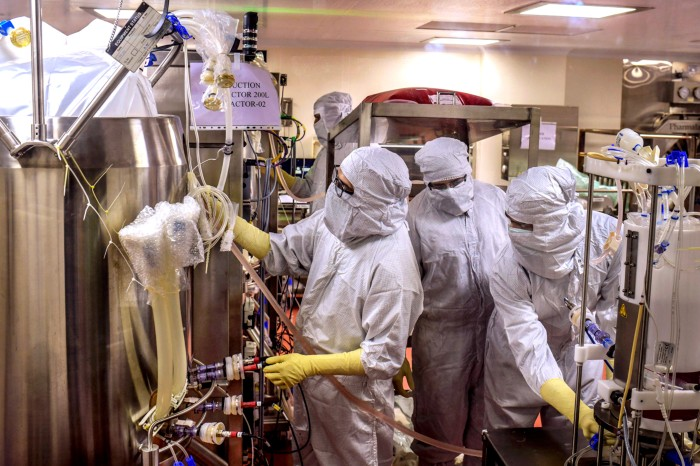 Three workers in protective clothing work on a bioreactor in a vaccine producing facility in Pune, India