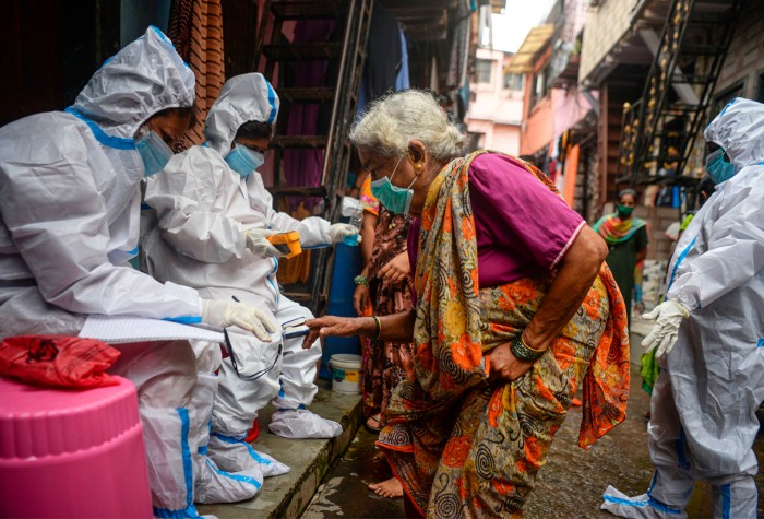 Health workers wearing coveralls and masks check the temperature of an elderly woman in the Dharavi slum in Mumbai