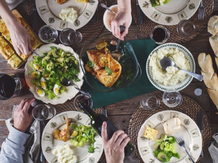 Overhead shot of lots of full plates on a table, with hands reaching to take food or pour wine.