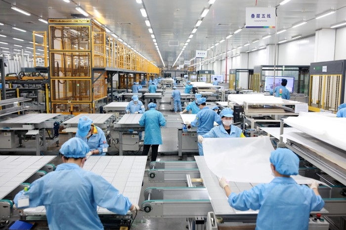 Employees work on photovoltaic solar panels at a factory in China