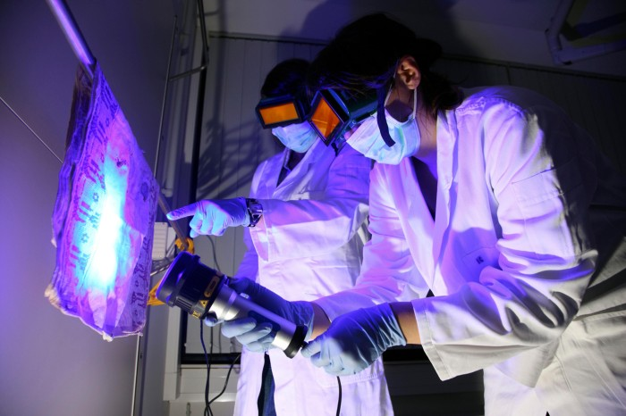 Two people wearing orange tinted goggles, lab coats and gloves use a UV torch to find traces of DNA on a piece of fabric