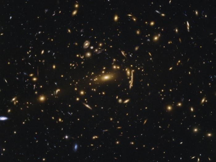 Yellow, white and blue galaxies against a black background.