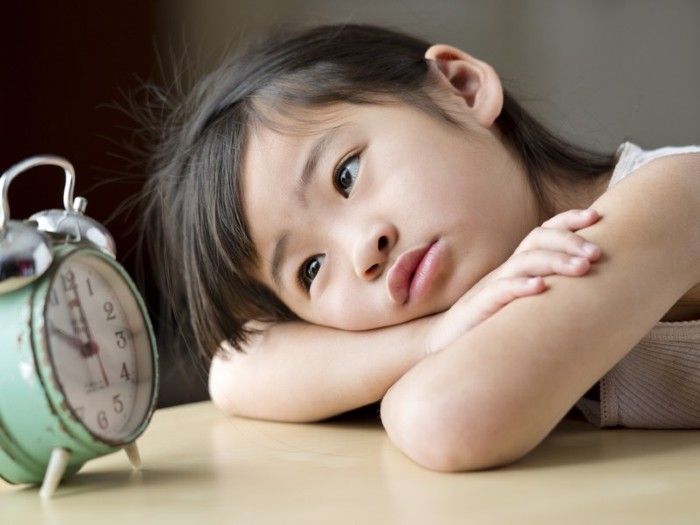 Portrait of a little girl sitting with her head on her arms, staring at an old clock.