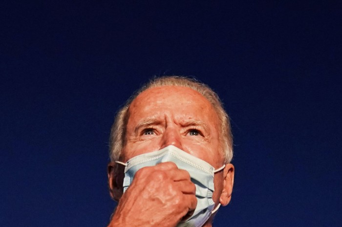 Close up of Joe Biden wearing a face mask looking into the distance on a deep blue background