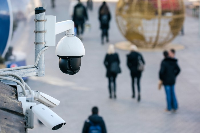 A spherical security camera overlooks a pedestrianised space with people walking past a large globe-shaped sculpture