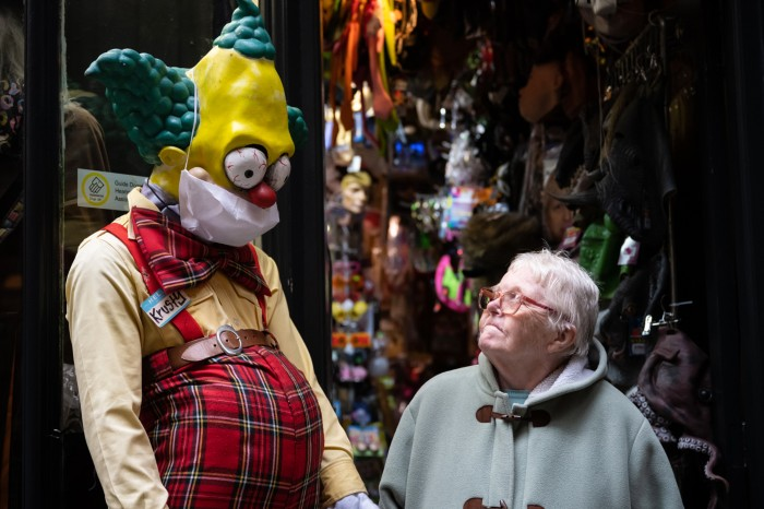 An elderly woman looks up at a large model of a clown character in a surgical face mask outside a fancy dress shop in Cardiff
