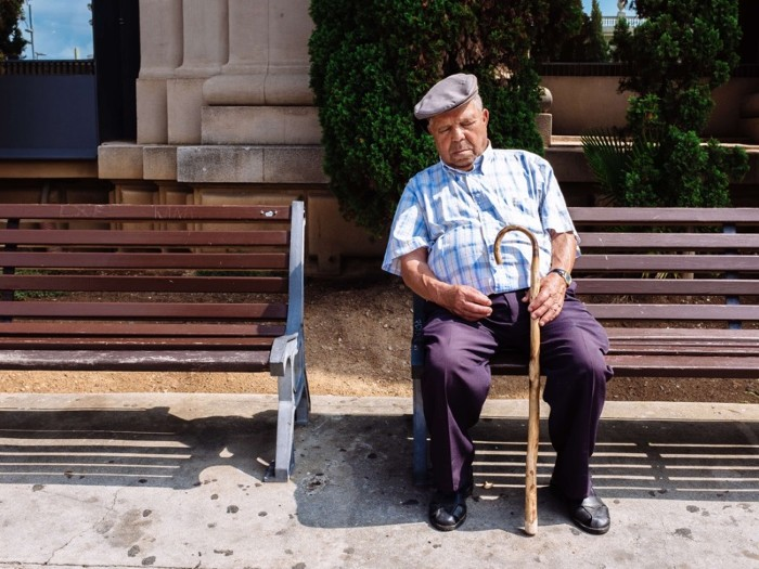Old men wearing a typical beret sleeping while sitting on a public bench.