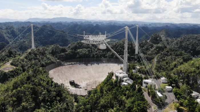 Wide aerial shot showing a hole in the main collecting dish of the Arecibo Observatory radio telescope.