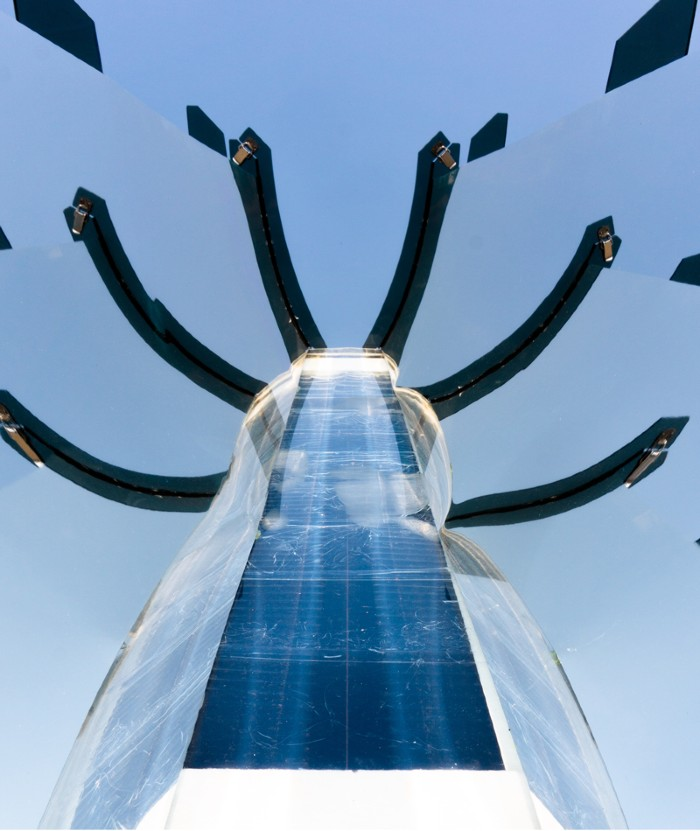 A solar collecting device with mirrors around a central core, framed against a blue sky.