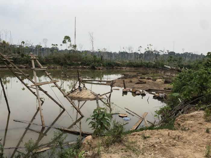 Artificial pond created when rainwater filled in an abandoned gold mining pit, Peruvian Amazon.