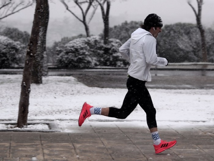 A man jogging on a snowy street.
