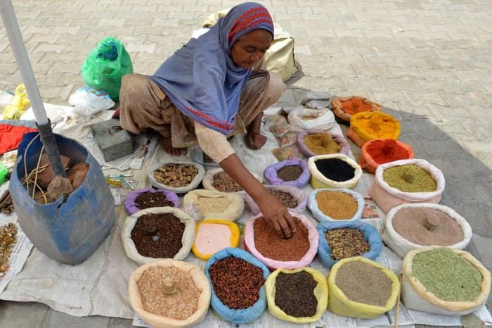 A woman displays bags of spices on a tarpaulin on the ground.