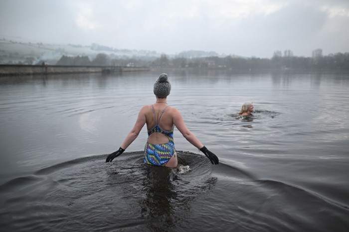 Individuals swimming in cold water outside.