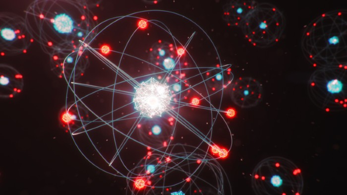 3D illustration of atomic structure, with red electrons orbiting blue and white nuclei.