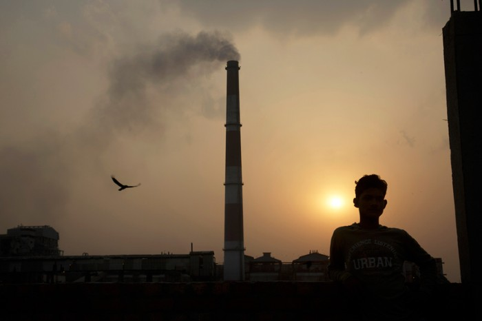 Emissions billow from smokestacks at a coal-fired power plant as the sun sets, India.