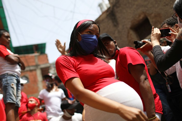 A heavily pregnant woman wearing a face masks and red t-shirt walks through a crowd amid feast day celebration in Venezuela