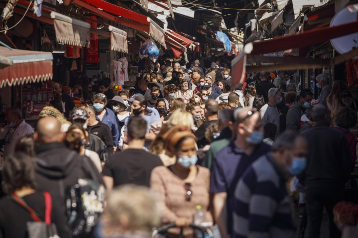 A narrow street in Tel Aviv filled with people, some wearing face coverings