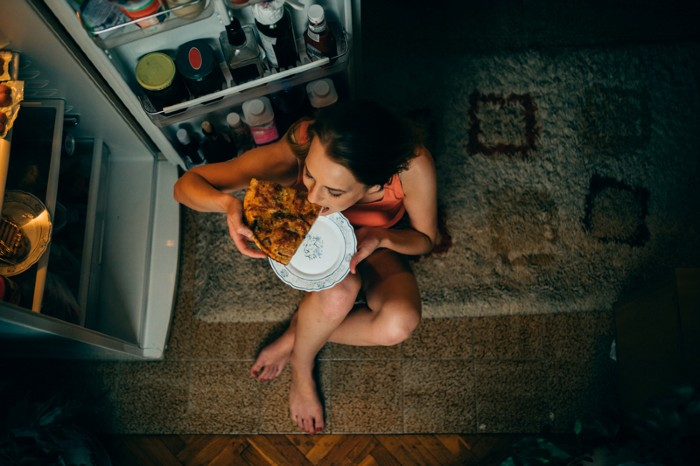 Woman eating in front of the refrigerator at night