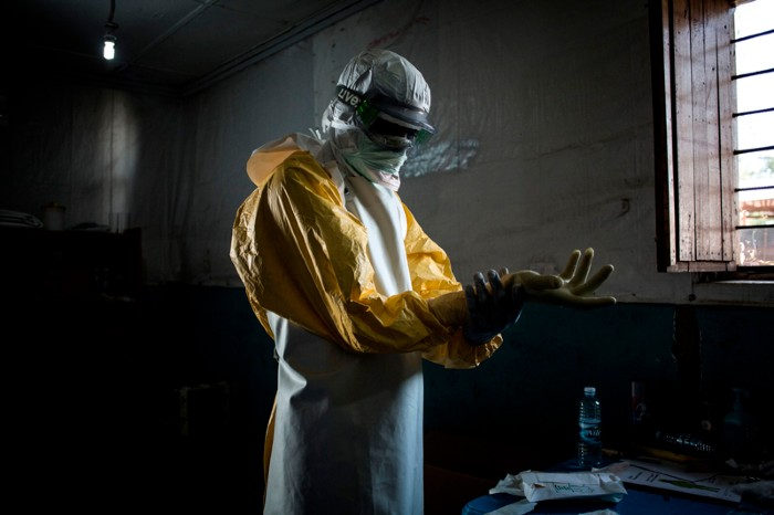 A health worker puts on his personal protective equipment