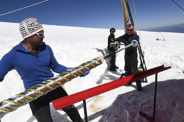 "Members of the ""Ice Memory project"" extract an ice core piece out of a drill machine"