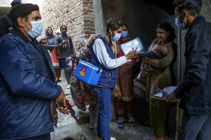 Armed police officers stand guard as a male health worker carrying a cool box administers a polio vaccine to baby in Pakistan