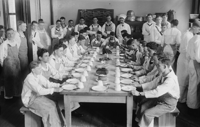 Midshipmen at dining table eat in formation, CIRCA 1900