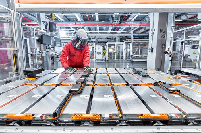 A worker wearing a face visor assembles an array of battery modules for an electric vehicle