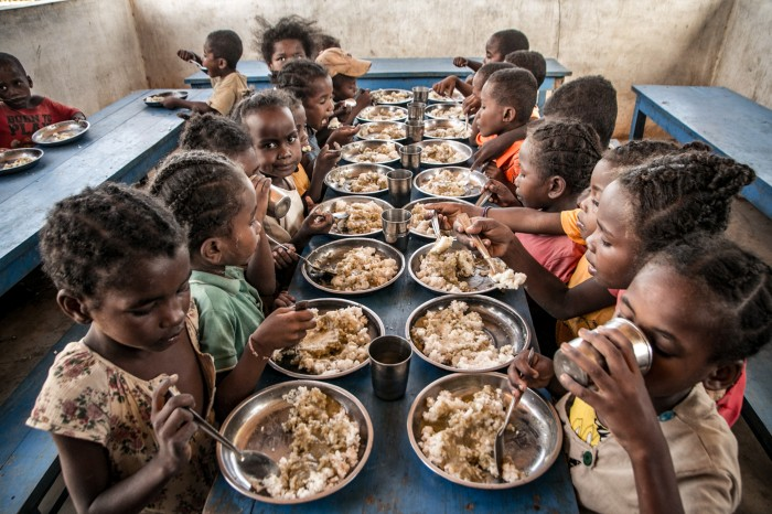 Primary school children sit at a long table eating their lunch in Madagascar