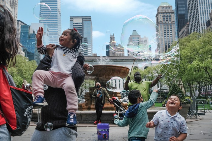 Children and adults play with bubbles in a park in a built up area of New York