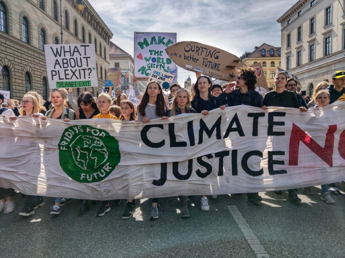 Demonstrators march with placards and banners reading 'Fridays for Justice' and 'Climate justice now', Munich 2019