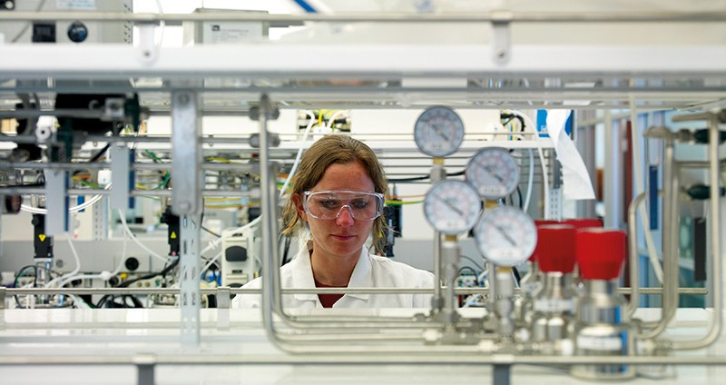 A female researcher looks at lab equipment