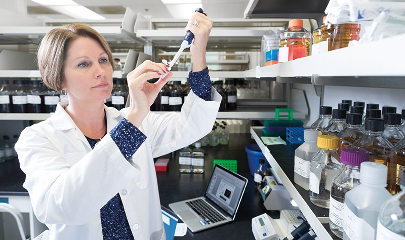 Immunologist Shannon Turley works in a lab with a pipette