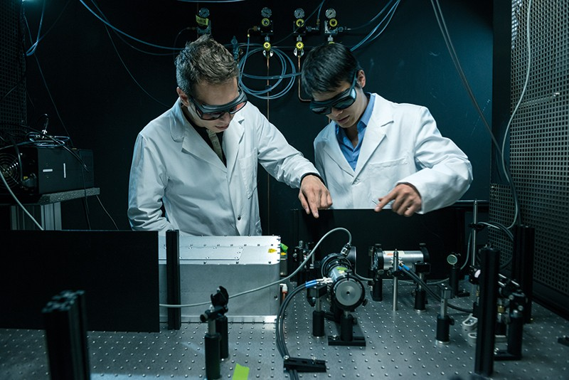 Two researchers examine an experimental laser set-up