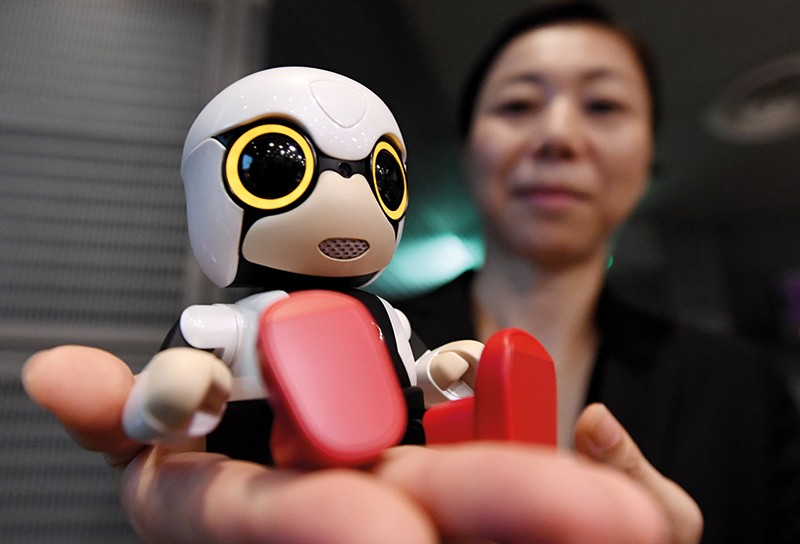 A woman holds a small robot in the palm of her hand