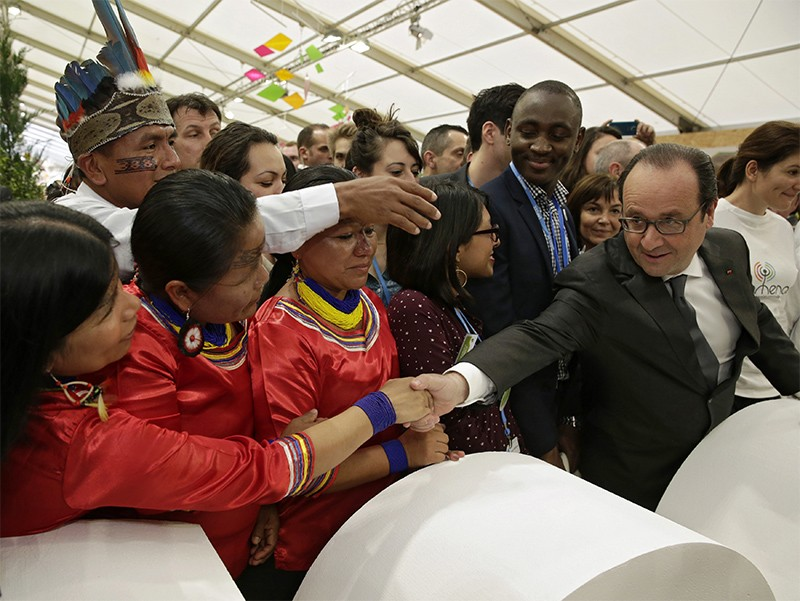 French President Francois Hollande shakes hands with visitors at COP21 in Paris.