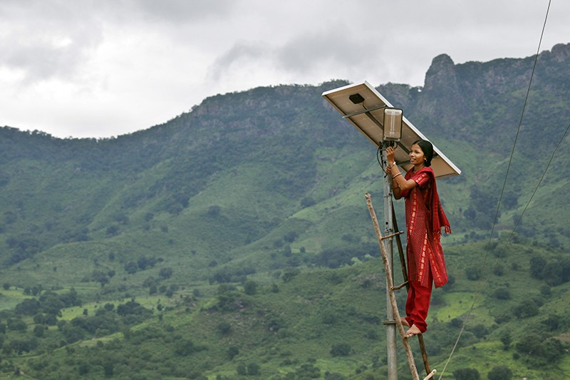 Person working on solar panel in India