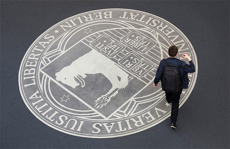 A student walks past the logo for the Free University of Berlin.