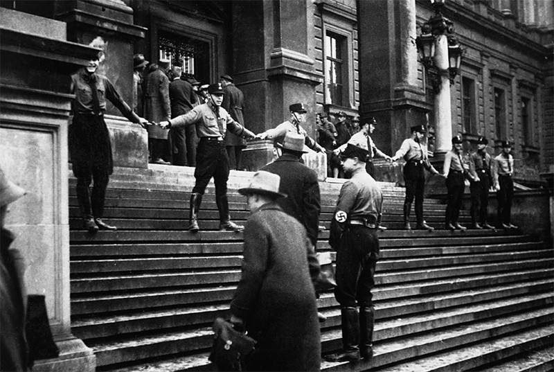 Nazi members link hands at the entrance of UNiv. Vienna to prevent Jewish people from entering. 1938.