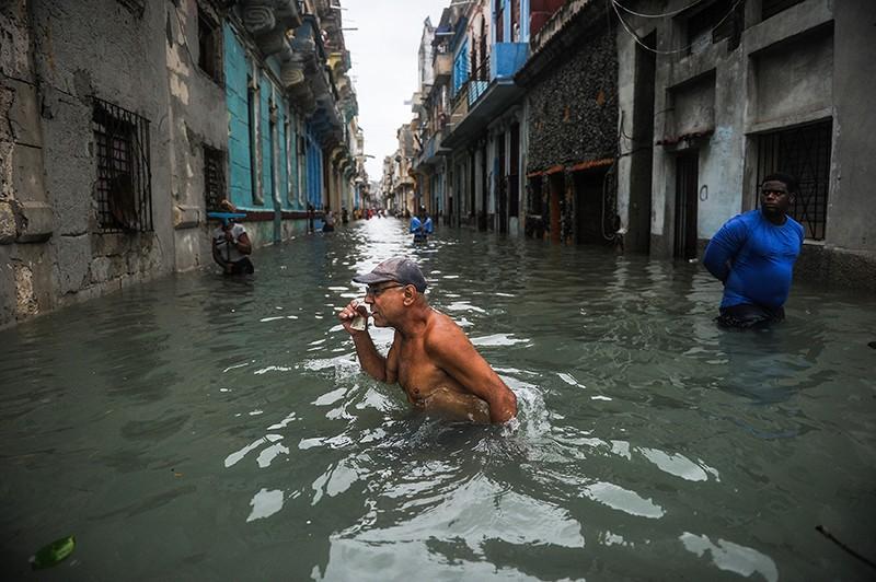 A Cuban wades through a flooded street in Havana